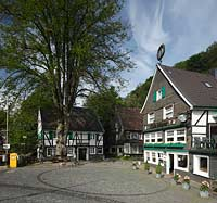 Solingen Unterburg, Schlossbergstrasse, Kopsteinpflasterplatz mit Briefkasten der Deutschen Post AG, Burger Brezelbaecker Denkmal, Stadtsparkasse Solingen und Cafe Meyer, Fachwerk- und Schieferhauser, Brezel auf dem Dach von dem Café; Solingen-Unterburg, Schlossbergstrasse, a place of cobble stone pavement, with a german letter box, Burger pretzel baker historical monument, cafe Meyer, with frame houses and houses of shist, a pretzel is on the roof of the café