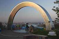"Kiew Blick vom Vladimirskaya Gorka Park durch den Bogen der Voelkerfreundschaft zwischen der Ukraine und Russland auf den Fluss Dnepr sowie die Hochhaeuser  am Westufer im roetlichen Licht der untergehenden Sonne . The friendship Arch: sculptor A. Skoblikov and Architect I. Ivanov and others. Dedicated to the unification of Russia and Ukraine, but called ""The Yoke"" by kievans. The rainbow shape arch is 50 metres in diameter. Viewing deck were most of the east bank can be viewed, Troeschina and towards the north of city. Podil and Obolon. Undemeath the Friendship Arch are two statues. The left one is made from bronze and depicts a Russian and Ukrainian worker holding up the Soviet Order of Friendship of People the other one is made from granite and depicts the particants of the Pereyaslavska Rada of 1654."